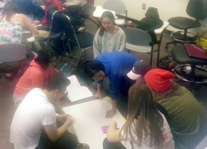 Photo of a group of college students seated on the floor and working on a map together